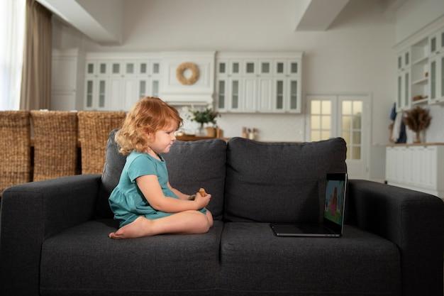 Pełne ujęcie słodkie dziecko siedzące na kanapie z laptopem