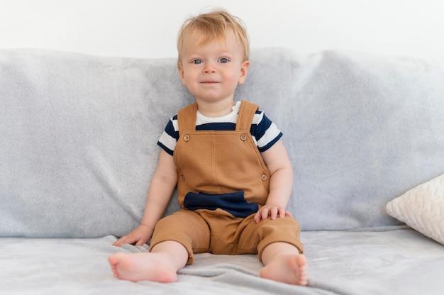 Pełne ujęcie słodkie dziecko siedzi na kanapie
