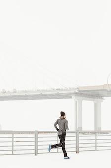 Pełne ujęcie sprawnego człowieka biegnącego na zewnątrz