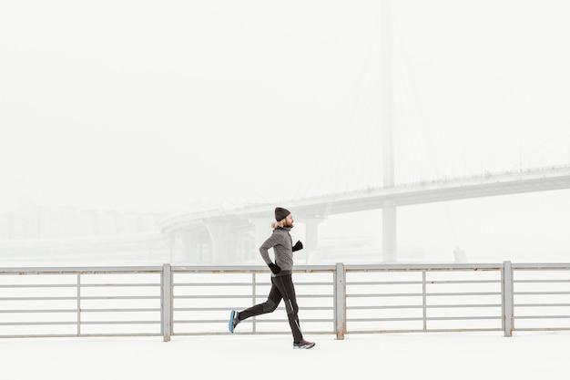 Pełne ujęcie sprawny mężczyzna biegnie samotnie