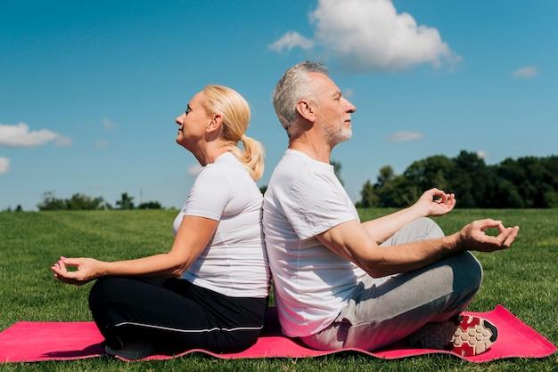 Pełne ujęcie starych ludzi medytujących razem