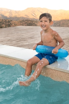 Pełne ujęcie szczęśliwe dziecko z kołem ratunkowym