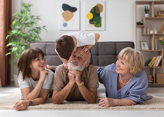 Pełne ujęcie szczęśliwej rodziny na podłodze w pomieszczeniu
