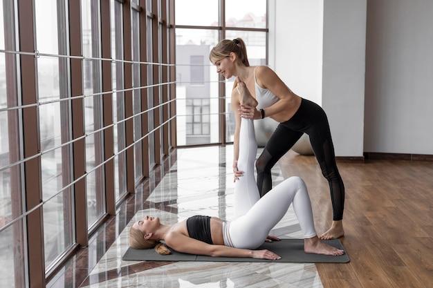 Pełne ujęcie trenera pomagające kobiecie poćwiczyć