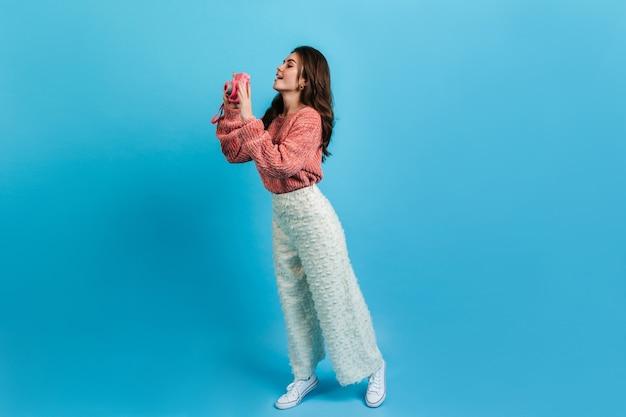 Pełne ujęcie uroczej brunetki w białych spodniach i różowym swetrze. dziewczyna z zainteresowaniem robi zdjęcie na instax.