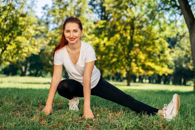 Pełne ujęcie uśmiechnięta kobieta ćwiczeń