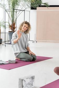 Pełne ujęcie uśmiechnięta kobieta siedzi na macie do jogi
