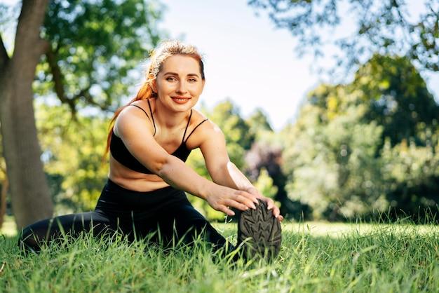 Pełne ujęcie uśmiechnięta sprawna kobieta ćwiczeń