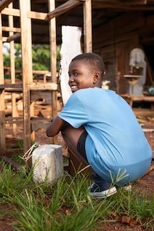 Pełne ujęcie uśmiechnięte dziecko na zewnątrz