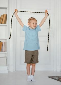 Pełne ujęcie uśmiechniętego chłopca trzymającego skakankę