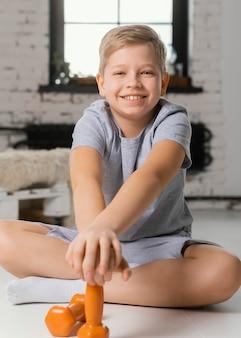 Pełne ujęcie uśmiechniętego dzieciaka z hantlami