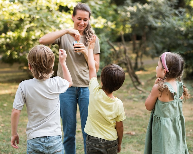 Pełne ujęcie uśmiechniętego nauczyciela i dzieci na zewnątrz