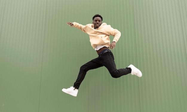 Pełne ujęcie uśmiechniętej nastolatki skaczącej