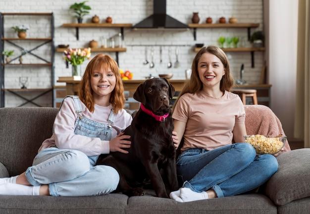 Pełne ujęcie uśmiechniętych kobiet i psa