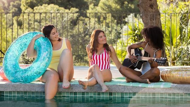 Pełne ujęcie uśmiechniętych przyjaciół na basenie