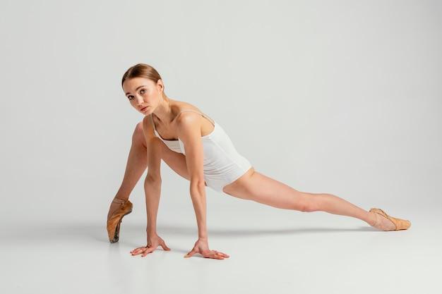 Pełne ujęcie utalentowanej kobiety robi szpagat