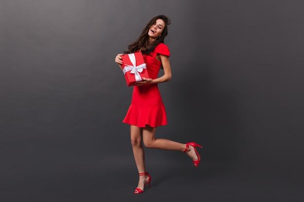 Pełne ujęcie wesołej, kręconej brunetki w mini sukience i na obcasach zalotnie unoszącej nogę. uśmiechnięta dziewczyna pozuje z pudełko na czarnym tle.