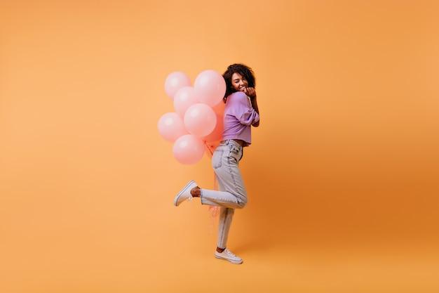 Pełne ujęcie wyrafinowanej szczupłej dziewczyny stojącej na jednej nodze i trzymającej balony. roześmiana ekstatyczna czarna kobieta tańczy po imprezie.
