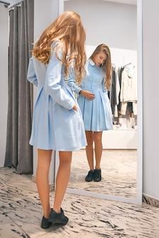 Pełne ujęcie z tyłu pięknej młodej kobiety patrzącej na siebie w lustrze podczas noszenia nowej sukienki w butiku z modą konsumpcjonizm styl życia detaliczny emocje kupującego trendy modny.