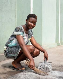 Pełne ujęcie zamiatanie afrykańskiej kobiety