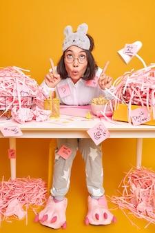 Pełne ujęcie zaskoczonej, oszołomionej azjatki w pozach nocnych w miejscu pracy pracuje w domowym biurze opracowuje nową strategię biznesową ma wiele zadań do wykonania wskazuje na koszty ogólne