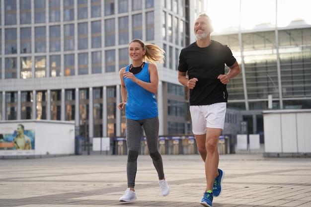 Pełne ujęcie zmotywowanej pary mężczyzny i kobiety w średnim wieku w strojach sportowych biegnących razem w