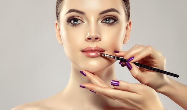 Pełne wdzięku dłonie profesjonalnego mistrza makijażu z wypielęgnowanymi paznokciami malują usta wspaniałej młodej kobiety tworzenie makijażu w toku