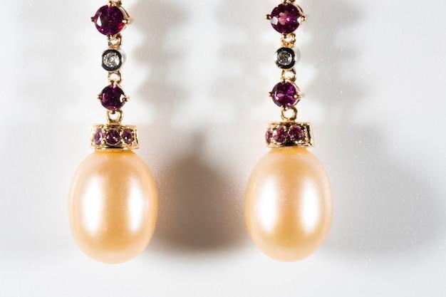 Pełne wdzięku złote kolczyki z brylantami, masa perłowa na białym tle