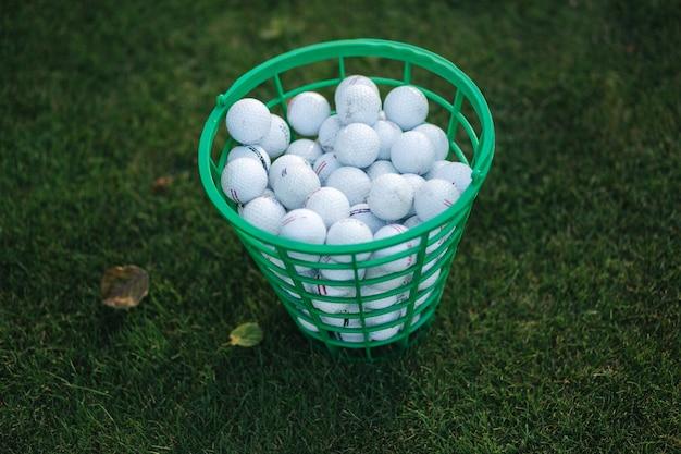 Pełne wiadro piłeczki do golfa na polu golfowym.