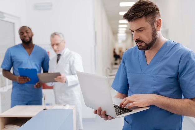 Pełne zainteresowania. dojrzały, skoncentrowany, profesjonalny lekarz pracujący w klinice i stojący w pobliżu gabinetu pielęgniarki podczas korzystania z laptopa