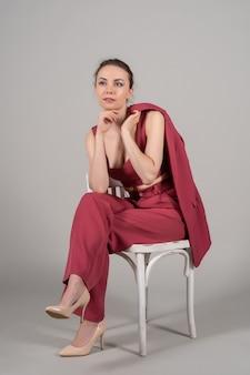 Pełne zdjęcie atrakcyjnej eleganckiej kobiety biznesowej siedzi na krześle w czerwonym garniturze na wysokich obcasach na białym tle szarym