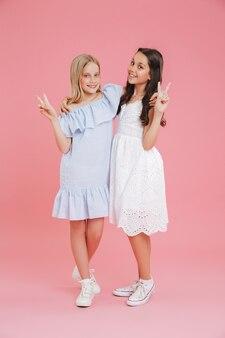 Pełne zdjęcie brunetki i blondynki ubranych w sukienki, uśmiechnięte i patrząc w kamerę, pokazując znak zwycięstwa, odizolowane na różowym tle
