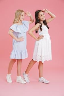 Pełne zdjęcie brunetki i blondynki ubranych w sukienki, uśmiechnięte i spoglądające daleko z rękami na czole, odizolowane na różowym tle