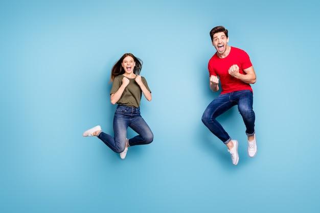 Pełne zdjęcie ciała ekstatycznych dwojga ludzi małżonkowie wygrywają na loterii skok podnoszą pięści krzycz tak nosić zielony czerwony t-shirt dżinsy dżinsy trampki odizolowane na niebieskim tle