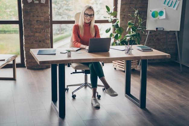 Pełne zdjęcie ciała odnoszącej sukcesy, uroczej kobiety właścicielki firmy, siedzącej przy stole do pracy na laptopie, wykonującej projekt startowy, nosić czerwony golf w biurowym miejscu pracy na poddaszu