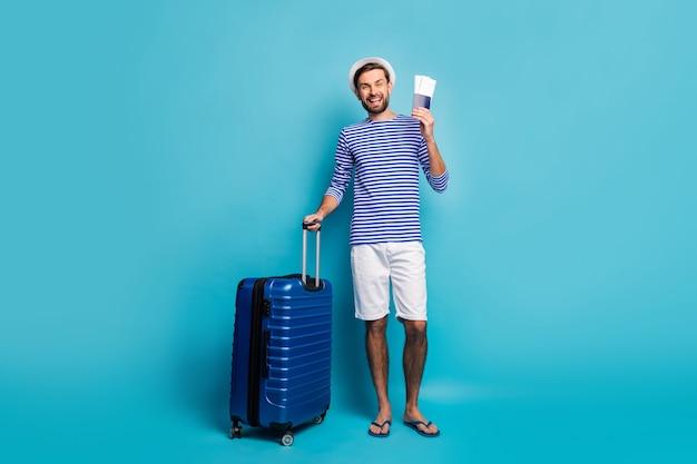 Pełne zdjęcie ciała przystojnego faceta uzależnionego od podróżnika pokaz biletów odprawa lotnicza walizka na kółkach nosić marynarską koszulę w paski kamizelkę spodenki panama klapki na białym tle niebieski kolor