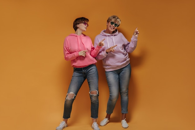 Pełne zdjęcie dwóch kobiet z krótkimi włosami w jasnych okularach przeciwsłonecznych, liliowo-różowych bluzach z kapturem i dżinsach, pokazujące miejsce na tekst na pomarańczowym tle.