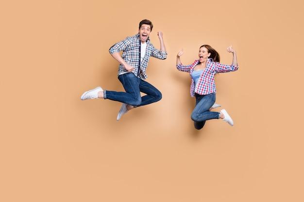 Pełne zdjęcie dwóch osób szalona pani facet skaczący wysoko, podnosząc kciuki do góry świętując udaną wygraną nosić casualowe dżinsy w kratę ubrania izolowane beżowe tło