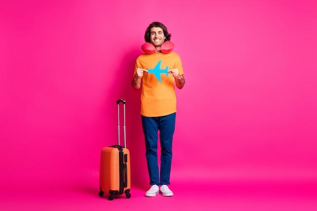 Pełne zdjęcie faceta z bagażem pokazuje papierowy samolot nosić poduszki na szyję pomarańczowy t-shirt dżinsy trampki na białym tle różowy kolor tła