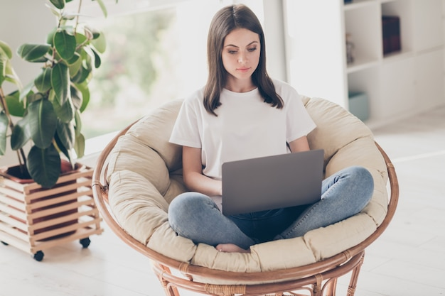 Pełne zdjęcie inteligentnej dziewczyny do pracy na laptopie siedzieć w wiklinowym krześle nosić dżinsy w domu w domu