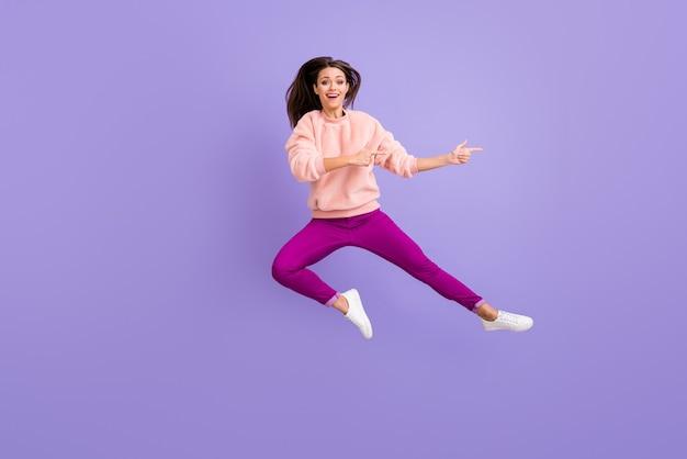 Pełne zdjęcie kobiety skaczącej wysoko, wskazując palcami puste miejsce na fioletowej ścianie