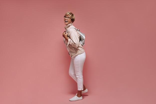 Pełne zdjęcie kobiety z krótkimi włosami i okularami w obcisłych, lekkich spodniach, białych tenisówkach i kurtce, śmiejącej się i trzymającej torbę na różowym tle.