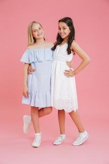 Pełne zdjęcie księżniczek dziewcząt ubranych w sukienki, uśmiechając się i patrząc na kamery, przytulając się razem, odizolowane na różowym tle