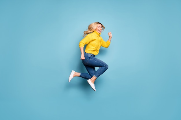 Pełne zdjęcie ładnej blond pani skaczącej w pośpiechu w centrum handlowym rabaty niskie ceny zakupy nosić dzianiny żółty sweter dżinsy izolowane niebieski kolor ściany