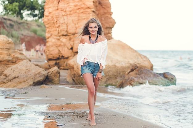 Pełne zdjęcie ładnej blondynki z długimi włosami spacerującej po plaży w pobliżu morza. ona uśmiecha się do kamery.