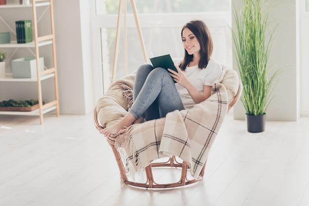 Pełne zdjęcie ładnej dziewczyny siedzi wiklinowym krześle i czyta książkę w nowoczesnym pokoju domowym