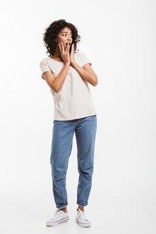 Pełne zdjęcie młodej amerykanki z brązowymi zamkami, patrzącej na bok i chwytającej twarz rękami ze strachu lub zaskoczenia, odizolowane na białej ścianie