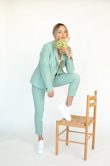 Pełne zdjęcie młodej blondynki w miętowym spodniach z hortensją w dłoniach przy krześle
