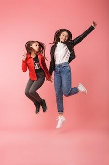 Pełne zdjęcie optymistycznych dziewcząt w swobodnym skakaniu razem, odizolowane na czerwonej ścianie
