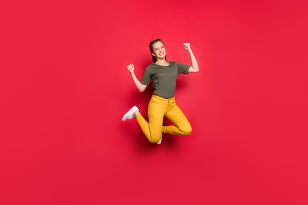 Pełne zdjęcie podekscytowanej tysiącletniej pani skaczącej w wesołym nastroju wspierającym ulubioną drużynę piłkarską nosić dorywczo żółte spodnie zielony t-shirt izolowany czerwony kolor tło